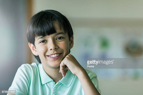 Portrait of cute smiling student with hand on chin