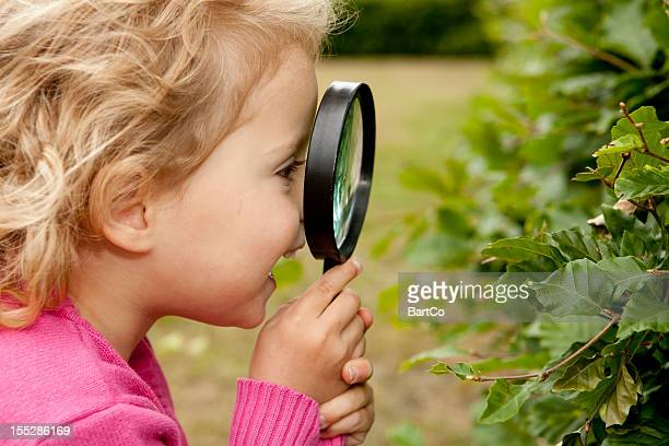 Portrait of cute toddler, magnifying glass
