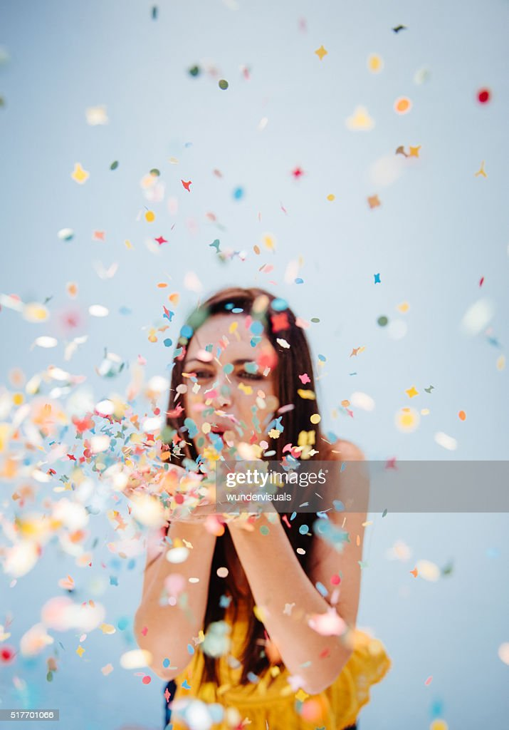 Portrait of  cute woman blowing confetti at holiday party : Stock Photo
