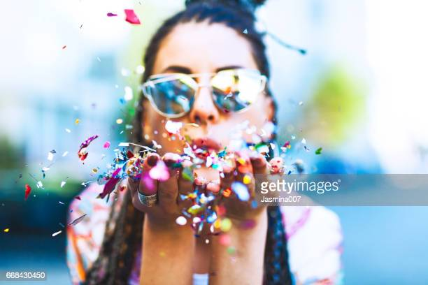 Portrait of cute woman blowing confetti