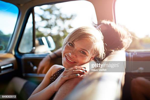 Portrait of cute woman in car, at sunset