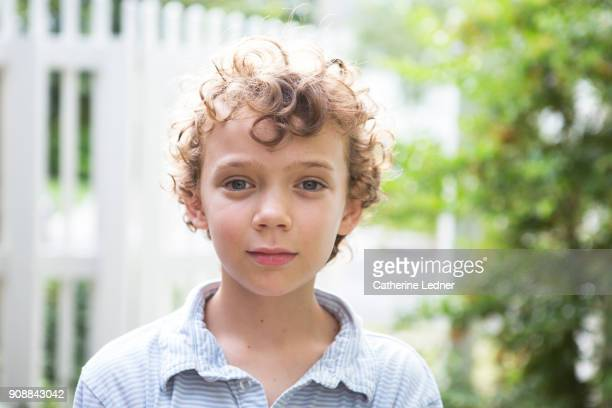 Portrait of cute young boy with blue eyes and curly blonde hair