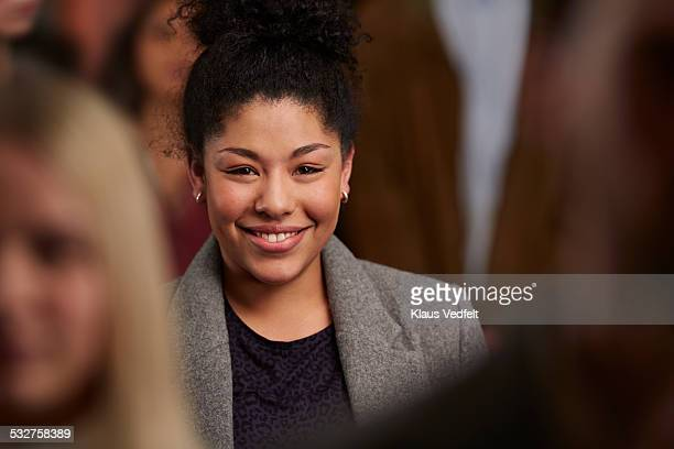 Portrait of cute young woman in crowd