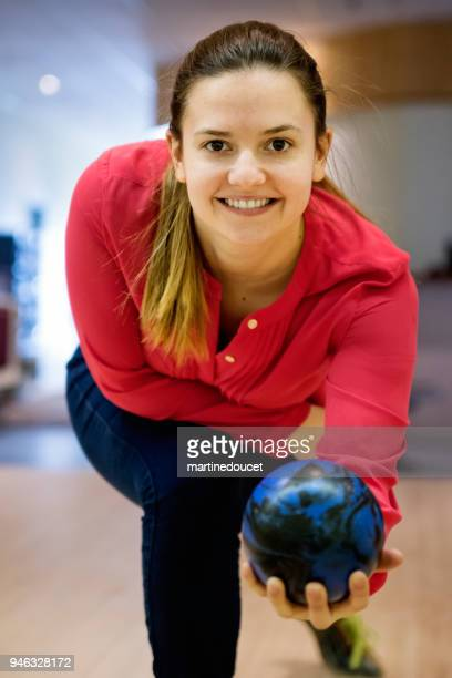 Portrait of cute young woman playing bowling.
