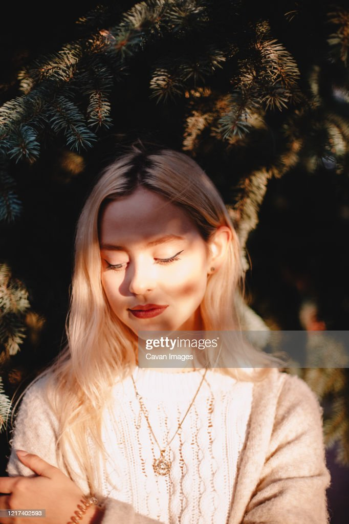 Portrait of cute young woman standing by Christmas tree against sun : Stock Photo