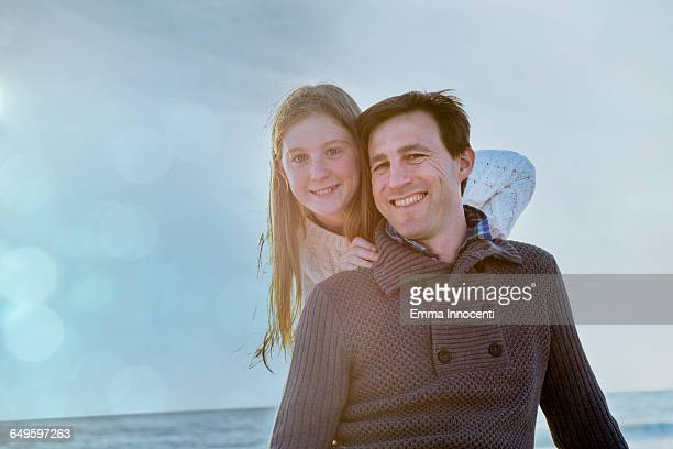 Portrait of dad and teenage daughter on the beach