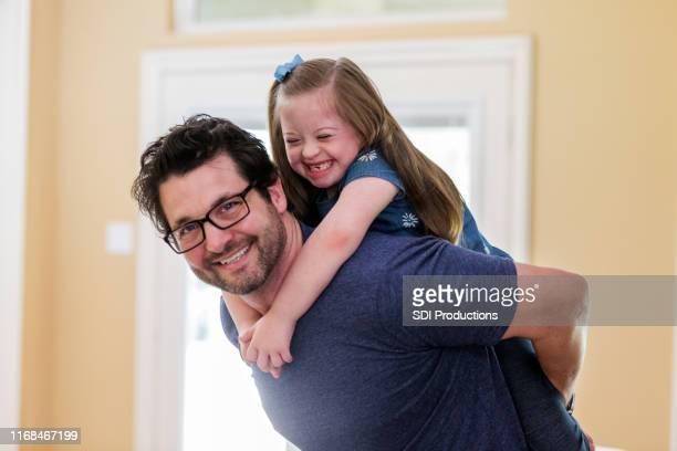 retrato de papá dando a la hija pequeña un paseo de regreso - discapacidad intelectual fotografías e imágenes de stock