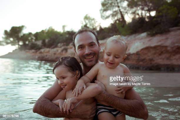portrait of dad with his two sons at the beach - chicos desnudos fotografías e imágenes de stock