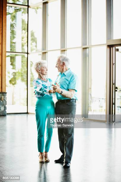 Portrait of dancing senior couple in community center