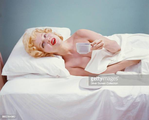 Portrait of Danishborn American model and actress Greta Thyssen as she lies seemingly nude in bed and holds a coffee cup late 1940s or early 1950s