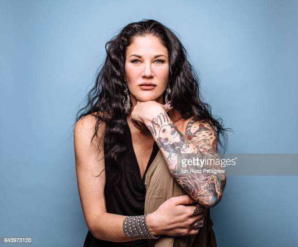 portrait of dark haired woman on blue background - tattooing stock photos and pictures