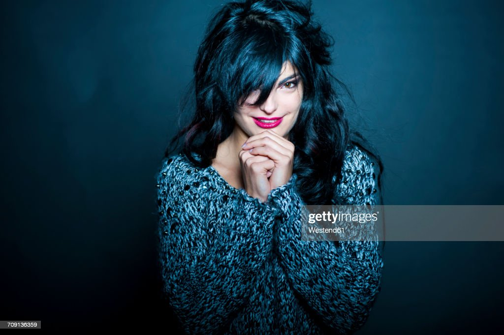 Portrait of dark-haired woman with red lips in front of dark background : Stock Photo
