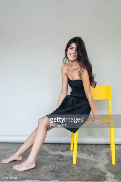 Portrait of dark-haired young woman sitting on yellow chair