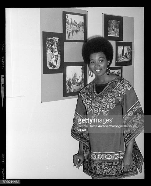 Portrait of Darlene Washington wearing afro and dashiki holding cigarette and standing next to photographic display of African dancers and wildlife...