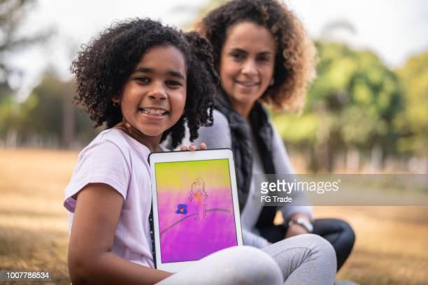 Porträt von Tochter und Mutter genießt einen Tag im Park mit Tablet