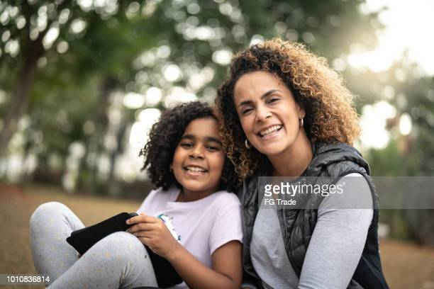 Portrait of Daughter and Mother Enjoying a Day at Park Using Tablet