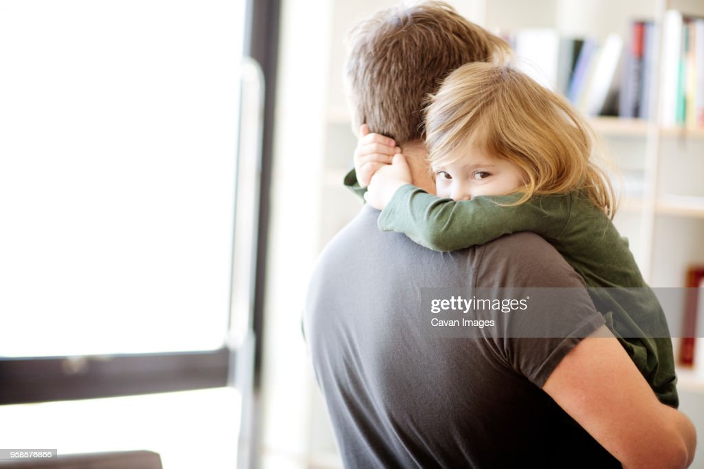 Portrait of daughter embracing father at home : Stock Photo