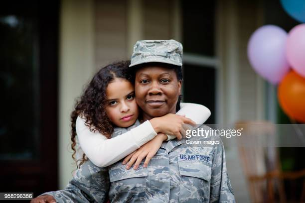 portrait of daughter embracing soldier against house - army soldier stock pictures, royalty-free photos & images