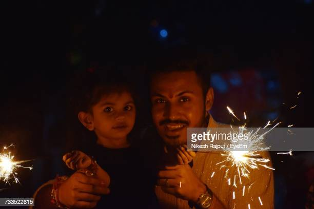 Portrait Of Daughter Holding Sparklers At Night During Diwali