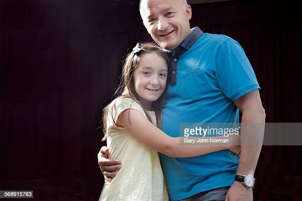 Portrait of daughter hugging dad.