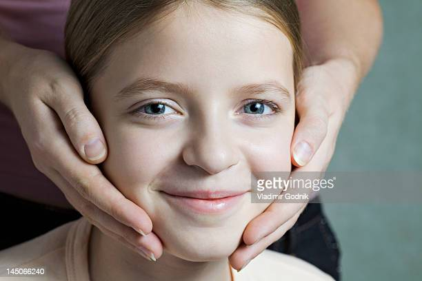 Portrait of daughter with Mother's hands on her cheeks