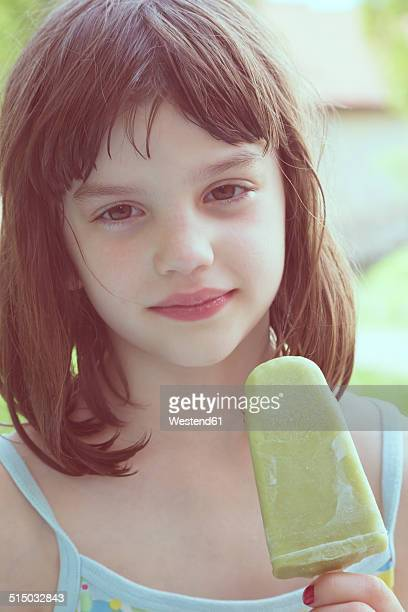 Portrait of daydreaming girl with green ice lolly
