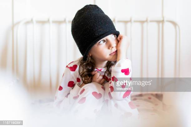 portrait of daydreaming little girl sitting in bed wearing cap and pyjama - membro parte do corpo - fotografias e filmes do acervo