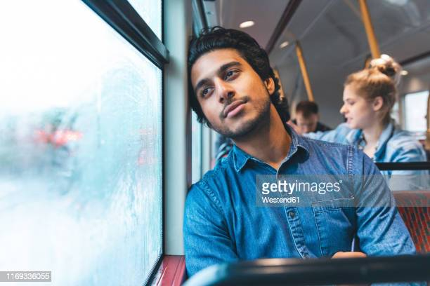 portrait of daydreaming young man travelling by bus, london, uk - denim stock pictures, royalty-free photos & images