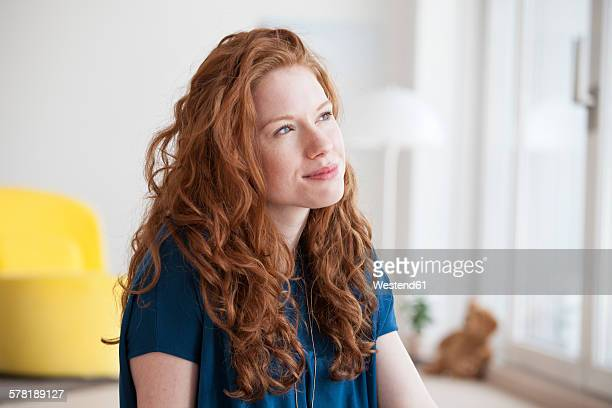 portrait of daydreaming young woman at home - seitenansicht stock-fotos und bilder