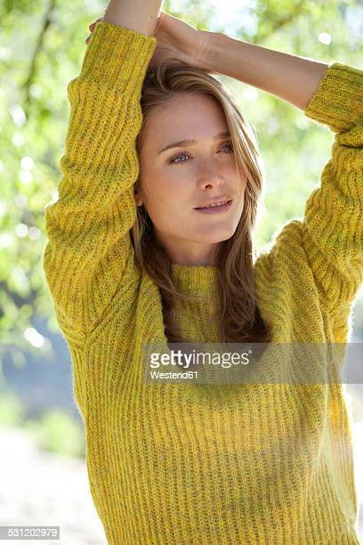 Portrait of daydreaming young woman wearing knit pullover