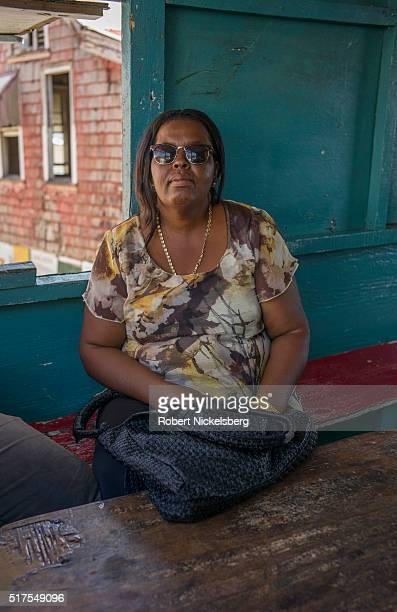 Portrait of Denise Duncan as she sits indoors on a red bench near Mount Royal, Carriacou island, Grenada, March 4, 2016.