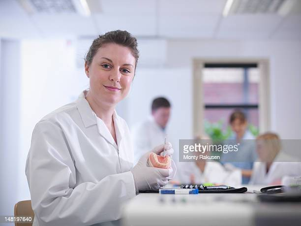 Portrait of dental apprentice working with model of teeth in dentist college
