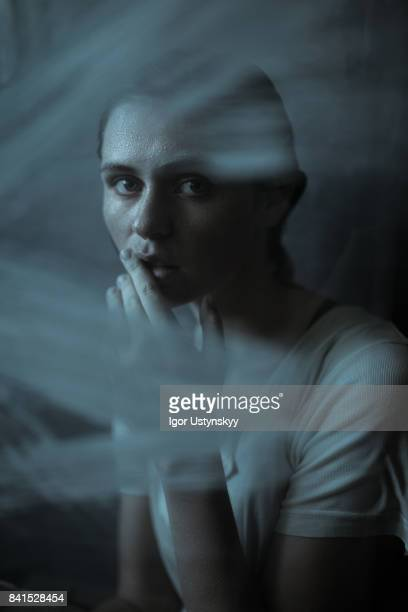 Portrait  of depressed woman indoors on the dark background