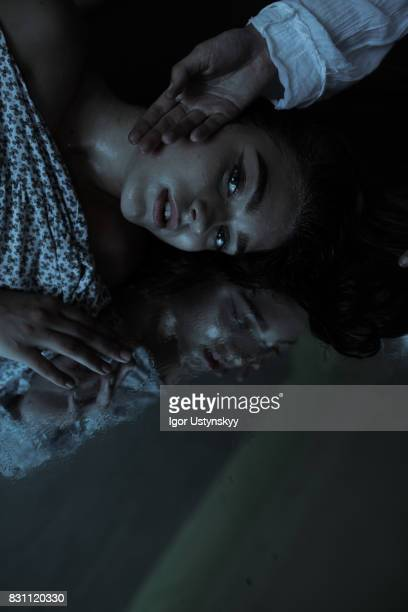 portrait  of depressed woman laying on mirror - one young woman only stock pictures, royalty-free photos & images