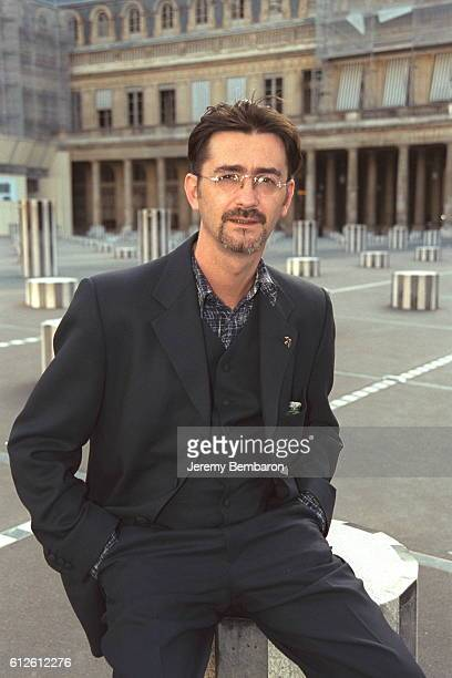 Portrait of designer Franck Sorbier in front of the Buren columns opposite the French Cultural Affairs Minister at the Palais Royal