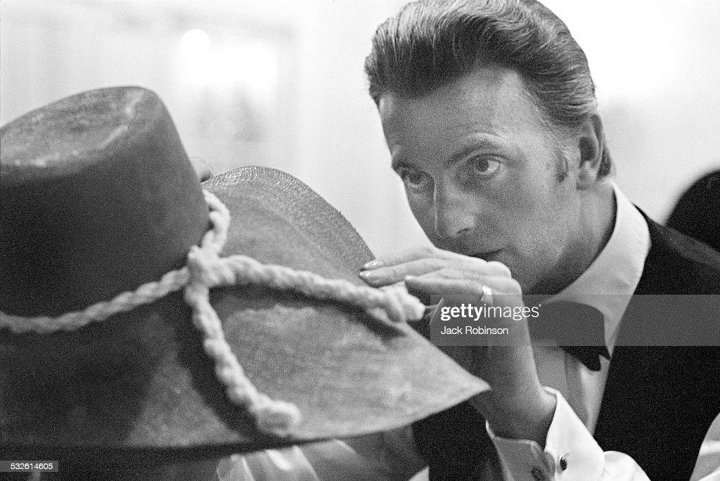 Portrait of designer Herbert de Givenchy as he adjusts his hat, 20th century.