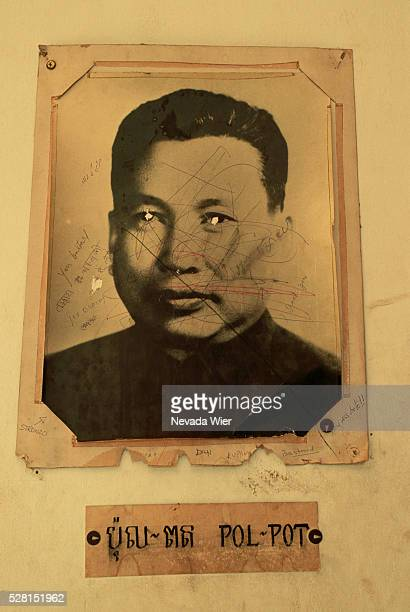 A portrait of dictator Pol Pot of the Khmer Rouge with holes poked in the eyes and graffti scrawled across it in the Tuol Sleng Museum