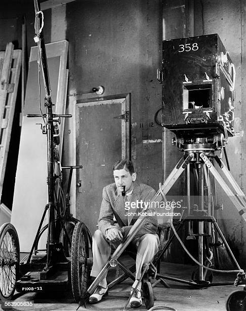 Portrait of director John Cromwell smoking a pipe as he sits on a film set circa 1939