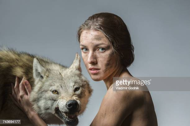 portrait of dirty naked woman with wolf against gray background - loup blanc photos et images de collection