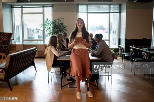 portrait of disabled amputee leader businesswoman using digital tablet at conference table - persons with disabilities stock pictures, royalty-free photos & images