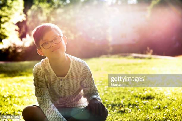 Portrait of disabled boy sitting on grassy field during sunny day