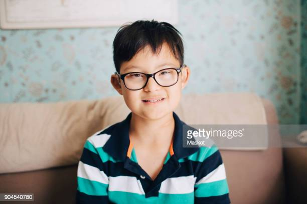 Portrait of disabled boy sitting on sofa against wall at home
