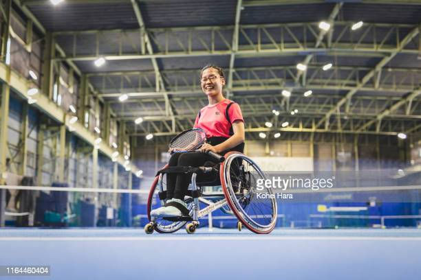 portrait of disabled female athlete playing wheel chair tennis - 車いすテニス ストックフォトと画像