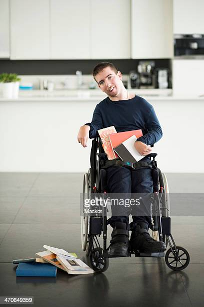 portrait of disabled man with books on wheelchair at home - paralisia cerebral - fotografias e filmes do acervo