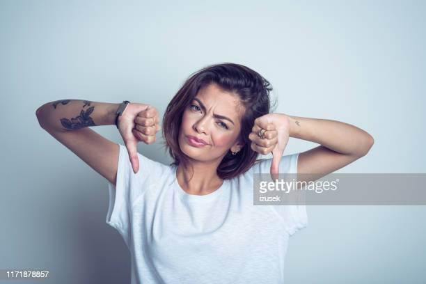 portrait of disappointed young woman standing with thumbs down - women's rights stock pictures, royalty-free photos & images