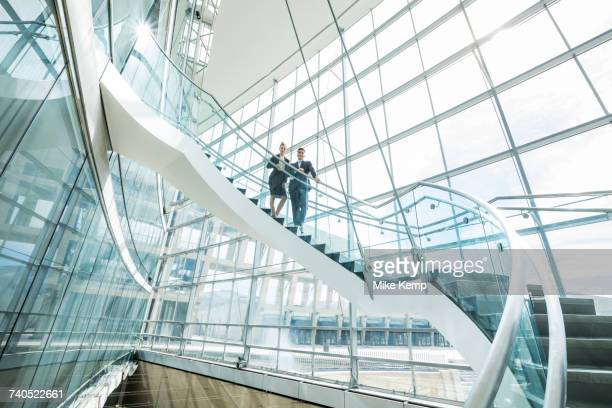 portrait of distant mixed race business people standing on staircase - human settlement stock pictures, royalty-free photos & images