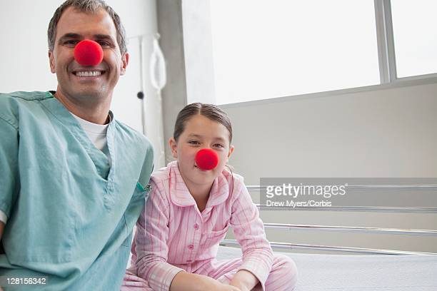 portrait of doctor and girl (10-12) sitting on hospital bed, wearing clown noses - clown's nose stock photos and pictures