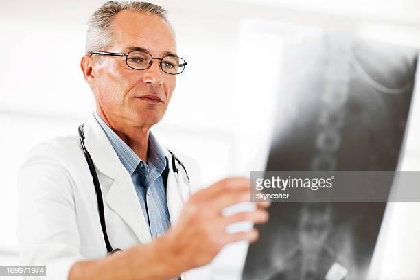 Retrato de médico examinar radiografías de columna.