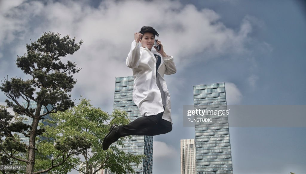 Portrait of doctor jumping and talking on cell phone : Stock-Foto