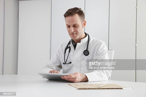 Portrait of doctor sitting by desk with digital tablet